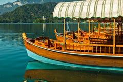 Le gondole di Pletna nel lago hanno sanguinato con una chiesa su una piccola isola in alpi slovene Immagini Stock