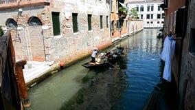 Le gondoliere stanno trasportando i turisti in una gondola stock footage