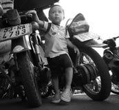 Le gosse grandit entre les motocyclettes à Hanoï Images libres de droits