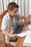 Le gosse élémentaire d'âge (8 ans) joue le jeu d'ordinateur Images libres de droits