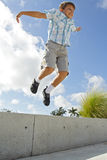 Le gosse sautant d'une saillie photographie stock libre de droits
