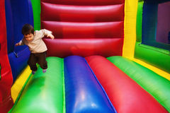 Le gosse sautant dans la cour de jeu gonflable Images libres de droits