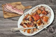 Le gourmet crachent fraîchement les tranches d'épaule de porc et les tranches de lard rôties de lard sur la planche à découper ré Photo libre de droits