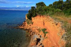 Le grès rouge unique bascule au-dessus de la petite plage pierreuse du côté norhern de l'île de Vir, Croatie, région adriatique photo stock