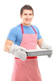 Le grabb som ha på sig det matlagningmittens och förklädet Royaltyfri Foto