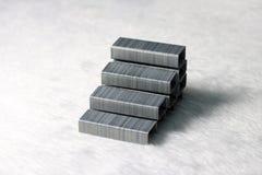 Le graffette del metallo hanno messo alla scala a forma di sul pavimento bianco del tessuto fotografie stock