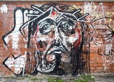 Le graffiti moderne de peinture sur un mur à Bucarest représentant Jesus Christ font face Photos stock