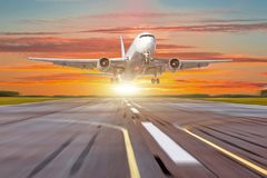Le grand avion dans le mouvement enlèvent l'aéroport du soleil de lever de soleil de coucher du soleil de ciel de soirée Photographie stock libre de droits