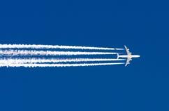 Le grand contrail d'aéroport d'aviation de quatre moteurs d'avion opacifie Photographie stock libre de droits