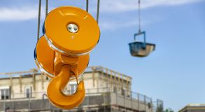 Le grand crochet devant un récipient bleu avec des matériaux de construction flotte au-dessus du chantier de construction avec la image stock