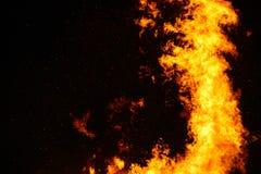 Le grand feu, br?lant et rougeoyant avec les flammes molles, miroite les agains volants le ciel fonc? Nuit de Walpurgis photos stock
