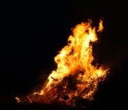 Le grand feu, br?lant et rougeoyant avec les flammes molles, miroite les agains volants le ciel fonc? Silhouette en bois rougeoya image stock