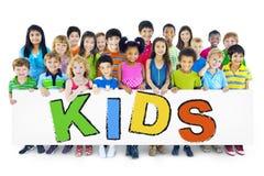 Le grand groupe d'enfants tenant le conseil badine le concept photos libres de droits