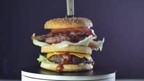 Le grand hamburger juteux avec deux tomates laitue et l'oignon de côtelettes qui est versé avec de la sauce tourne, concept de  banque de vidéos
