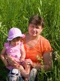 Le grand-mère avec le descendant grand s'asseyent dans un g Images stock