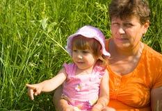 Le grand-mère avec le descendant grand s'asseyent dans un g Photos stock