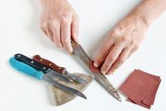 Le grand maître essaye d'affiler les couteaux de cuisine rouillés sur son De blanc Images stock