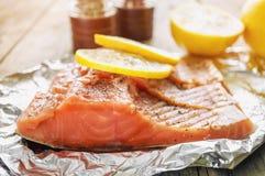 Le grand morceau rose de saumons avec les herbes et le citron se repose sur un morceau brillant d'aluminium Photos stock