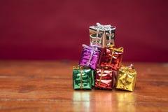 Le grand nombre de petits cadeaux sur une table en bois, fond rouge soit Images stock