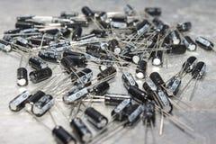 Le grand nombre des condensateurs sont situés sur une table d'ordinateur Image stock