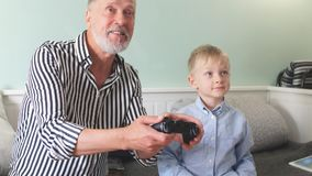 Le grand-père émotif joue avec son petit-fils dans des jeux d'ordinateur avec une manette clips vidéos
