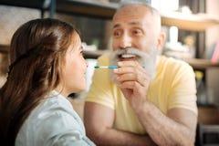 Le grand-père étant sur le point mettre le point de peinture sur des petite-filles flairent Images stock