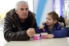Le grand-père avec son petit-fils ont la crème glacée  Image stock