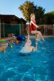 Le grand-père d'une chevelure blanc jette sa petite-fille dans le Swimmin photos stock
