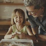 Le grand-père de petite fille font le concept cuire au four de biscuit photo libre de droits