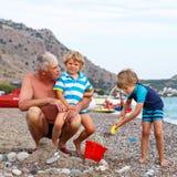 Le grand-père et deux garçons de petit enfant sur l'océan échouent photographie stock