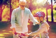 Le grand-père et le garçon avec la bicyclette à l'été se garent Image libre de droits