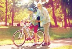 Le grand-père et le garçon avec la bicyclette à l'été se garent Photos libres de droits