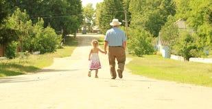 Le grand-père et la petite-fille sont sur la route Image libre de droits