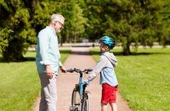 Le grand-père et le garçon avec la bicyclette à l'été se garent Photographie stock libre de droits
