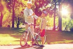Le grand-père et le garçon avec la bicyclette à l'été se garent Images libres de droits
