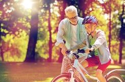 Le grand-père et le garçon avec la bicyclette à l'été se garent Photo stock
