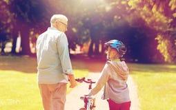 Le grand-père et le garçon avec la bicyclette à l'été se garent Photographie stock