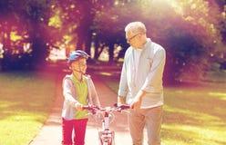Le grand-père et le garçon avec la bicyclette à l'été se garent Images stock