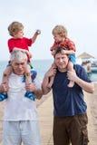 Le grand-père et le père donnant deux garçons montent sur des épaules Photographie stock