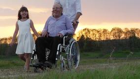Le grand-père handicapé est conduit dans un fauteuil roulant banque de vidéos