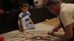 Le grand-père joue avec son petit-fils dans un chemin de fer en bois sur le plancher Un petit garçon de trois ans avec le grand-p clips vidéos
