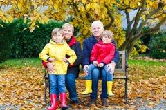 Le grand-père, la grand-mère et deux garçons de petit enfant, petits-enfants s'asseyant en automne se garent Images libres de droits