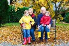 Le grand-père, la grand-mère et deux garçons de petit enfant, petits-enfants s'asseyant en automne se garent Photo libre de droits