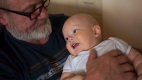 Le grand-père tient un petit petit-fils Un homme plus âgé avec une barbe grise et un petit garçon d'un an banque de vidéos