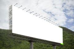 Le grand panneau d'affichage vide sur le fond de montagne verte et de ciel bleu, pour votre publicité, a mis votre propre texte i Photographie stock libre de droits