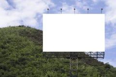 Le grand panneau d'affichage vide sur le fond de montagne verte et de ciel bleu, pour votre publicité, a mis votre propre texte i Images libres de droits
