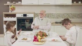 Le grand-papa communique avec des petits-enfants à la table avant un dîner de famille banque de vidéos