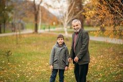 Le grand-papa et le petit-fils passent le temps en parc d'automne Ils s'étreignent et marchent Temps de Fmily image libre de droits