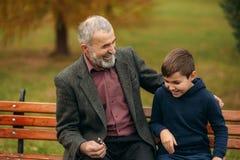 Le grand-papa et son petit-fils passent le temps ensemble en parc Ils se reposent sur le banc Marche en parc et photo stock