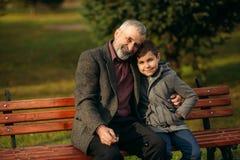 Le grand-papa et son petit-fils passent le temps ensemble en parc Ils se reposent sur le banc et s'étreignent photographie stock